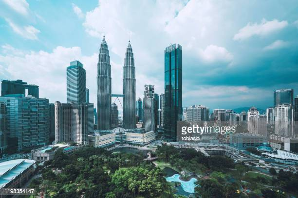 kuala lumpur skyline with petronas towers a clody afternoon - kuala lumpur stock pictures, royalty-free photos & images