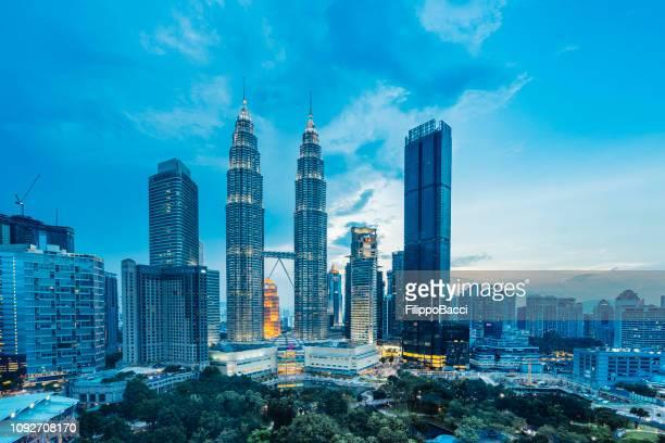 kuala lumpur skyline com petronas towers ao pôr do sol - torres petronas - fotografias e filmes do acervo