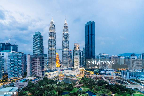 kuala lumpur skyline met de petronas towers bij zonsondergang - zonsopgangen en zonsondergangen stockfoto's en -beelden
