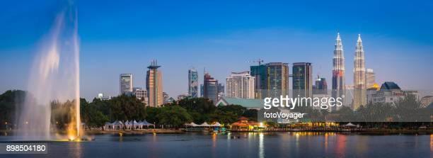 照らされたマレーシアのクアラルンプール高層ビル都市の景観パノラマ噴水やレストラン