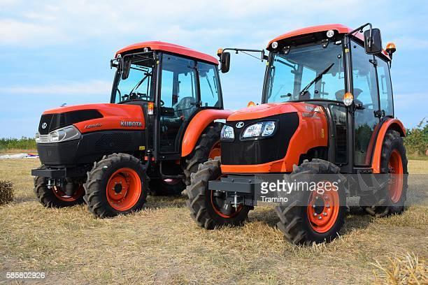 kubota tractors parked on the field - トラクター ストックフォトと画像