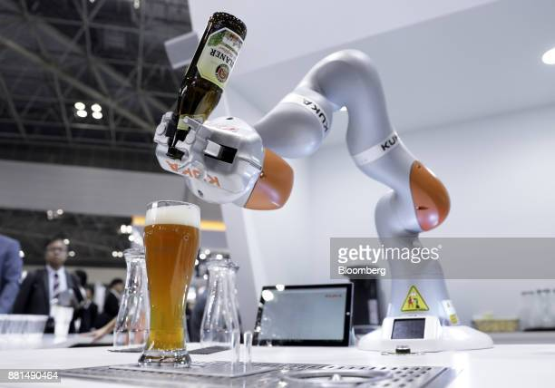 A Kuka AG LBR iiwa robotic arm pours a bottle of beer into a glass during a demonstration at the International Robot Exhibition in Tokyo Japan on...