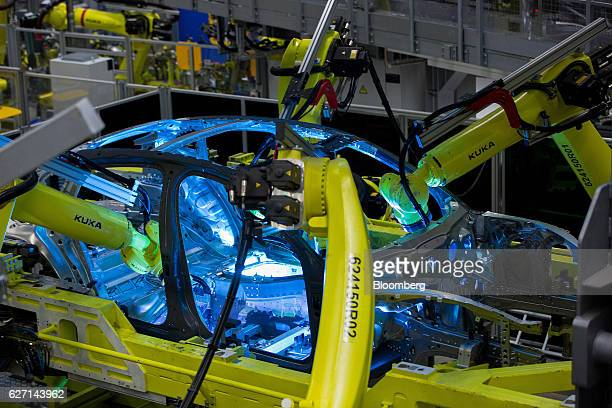 Kuka AG robotic arms operated on the body frame of a Porsche Panamera luxury automobile inside the Porsche Leipzig GmbH factory a unit of Porsche AG...