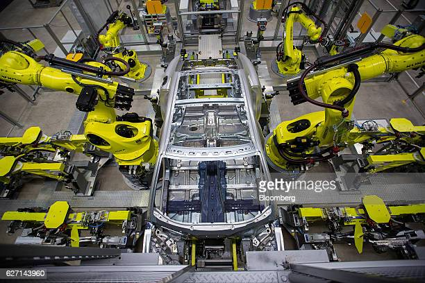 Kuka AG robotic arms stand around the body frame of a Porsche Panamera luxury automobile inside the Porsche Leipzig GmbH factory a unit of Porsche AG...