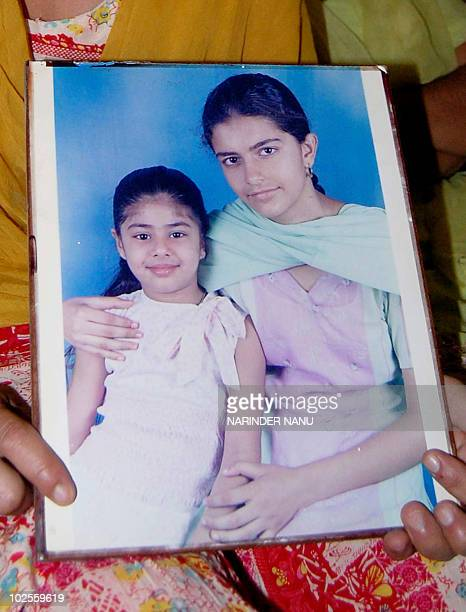 Kulbir Kaur an aunt to murdered 17year old Amritpal Kaur holds up a portrait photograph of her deceased niece posing with her cousin Simran at her...