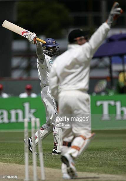 Kumar Sangakkara of Sri Lanka celebrates scoring 100 runs as Brendon McCullum of New Zealand celebates running out Muttiah Muralitharan on day three...