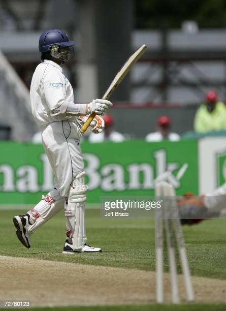 Kumar Sangakkara of Sri Lanka celebrates scoring 100 runs unaware of the run out of teammate Muttiah Muralitharan at the other end by Brendon...