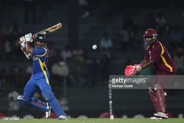 Kumar Sangakkara of Sri Lanka hits to the offside as wicketkeeper Darren Bravo looks on during the 2011 ICC World Cup warm up match between Sri Lanka...