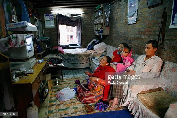 Kumari Devi Sajani Shakya watches TV with her family mother Rukmani fatherNhuchha and sisterSalina at their home on March 25 2007 in Bhaktapur Nepal...
