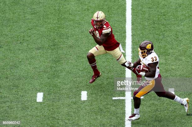 Kumehnnu Gwilly of the Central Michigan Chippewas carries the ball with pressure from Will Harris of the Boston College Eagles during the first...