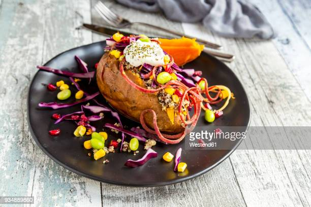 Kumpir, filled sweet potatoe, red cabbage, corn, edamame, carrots, quinoa, creme fraiche on plate