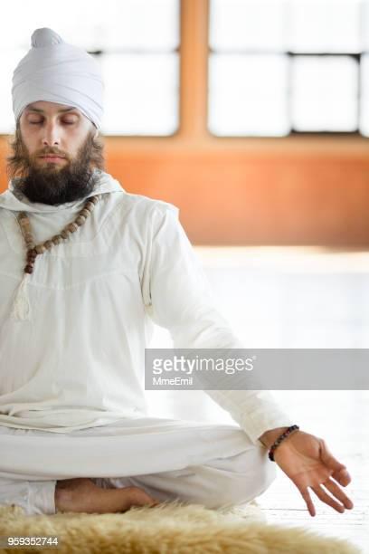 kundalini. man practicing yoga. meditating in lotus pose - yogi stock photos and pictures