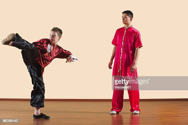 kung fu, changquan, ce chuai, long fist style, kung fu instructor and boy (10-11) - kicking ストックフォトと画像