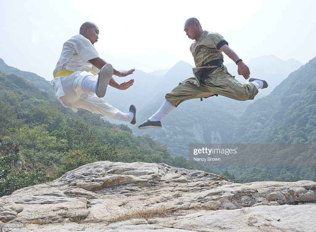 Man Practicing Shaolin Kung Fu With Wooden Pole Against