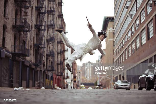 Kung fu martial artist doing a flying roundhouse kick