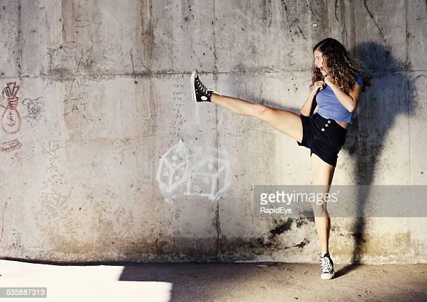 Kung-fu fighting? Gekräuseltes cutie hohe kicks energisch von stone wall