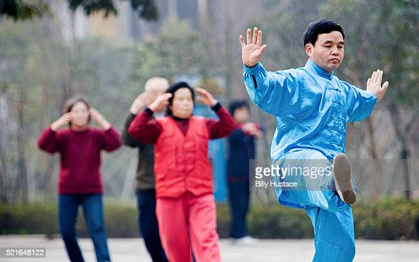 Kungfu teacher leading students in taiqiquan lessons in a park.