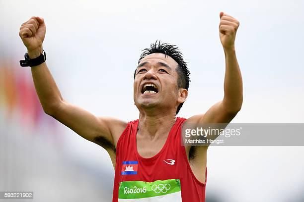 Kuniaki Takizaki of Cambodia reacts as he crosses the finish line during the Men's Marathon on Day 16 of the Rio 2016 Olympic Games at Sambodromo on...