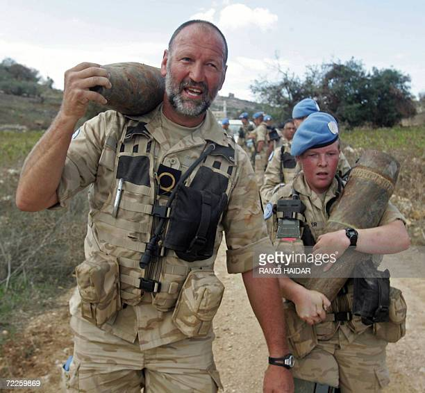 Belgian soldiers with the United Nations Interim Forces in Lebanon carry unexploded 155 mm Israeli bombs in the village of Kunin south Lebanon 25...