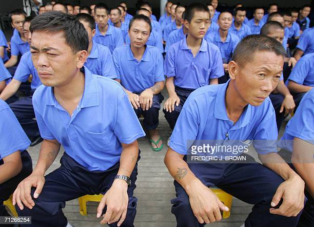 Drug rehab patients mostly recovering from heroin addiction sit in a courtyard at the Kunming Municipal Compulsory Rehabilitation Center in Kunming...