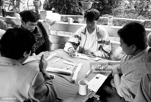 Kunming Yunnan People's Republic of China April 1997 Chinese people are playing Mahjong in a temple