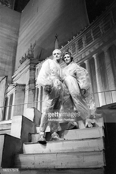 Kunt and Anna interpreted by Vittorio Gassman and Ilaria Occhini standing on the stairs and dressed with cellophane in a scene of 'Un marziano a...