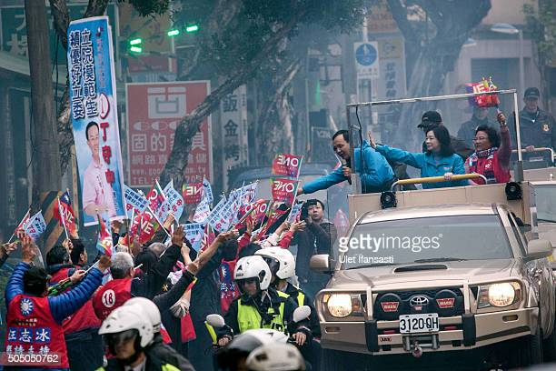 Kuomintang Party presidential candidate Eric Chu, waves to the supporters from a truck as he parades through the streets of Taiwan during rally...