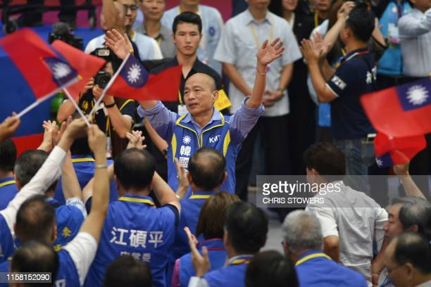 Kuomintang party's presidential candidate Han Kuoyu gestures to a crowd waving Taiwanese flags at the start of the KMT national congress in Taipei on...