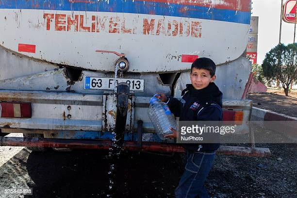 A Kurd refugge boy fills an empty bottle with drinking water in a refugge camp in the Turkish city of Suruc Sanliurfa province wich is located 6...