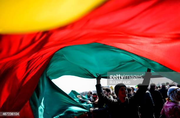 A Kurdiah man holds a large Kurdish flag during Newroz celebrations marking the Kurdish New Year on March 22 2015 in Istanbul Newroz which means 'new...