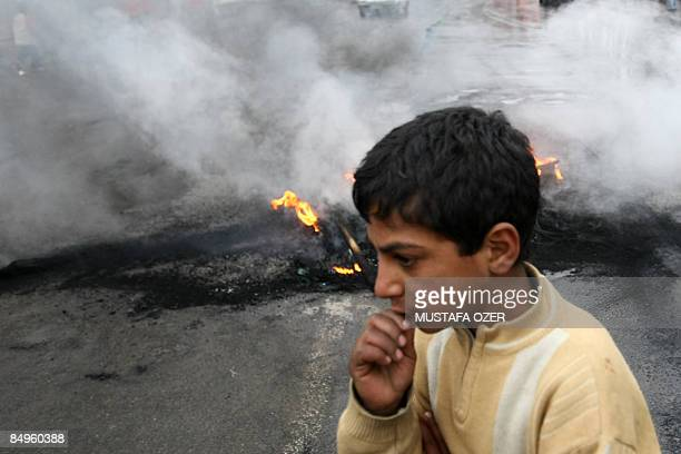 Kurdish boy passes by a fire that was set after a demonstration to protest Turkish Prime Minister Recep Tayyip Erdogan's up-coming local elections...