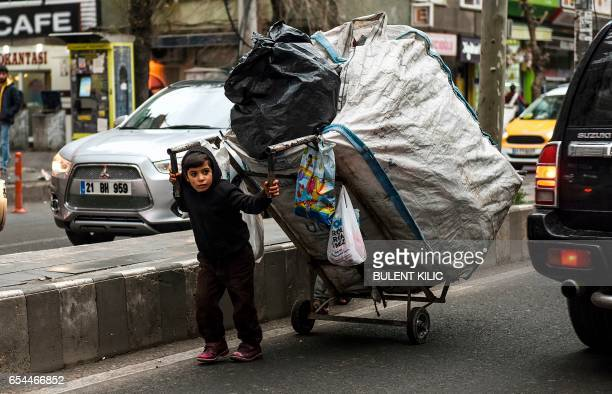 Kurdish boy pulls a card as he collects rubbish to make money in the center of Diyarbakir on March 17 2017 / AFP PHOTO / BULENT KILIC