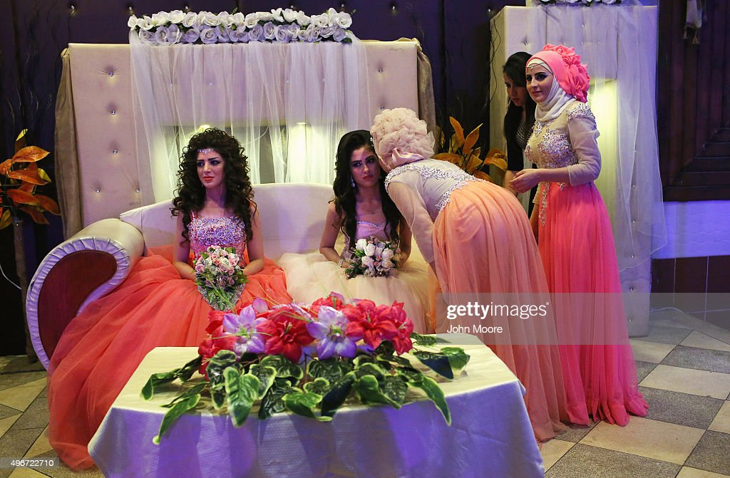 Kurdish brides Halbast Khalili, 21, (L), and Mezgin Murat, 21, (C), are greeted by the invited during their wedding reception without their grooms on November 11, 2015 near Qamishli, in the autonomous region of Rojava, Syria. They married their husbands in absentia two months after the brothers successfully immigrated to Germany in the arduous journey as refugees. The women plan to join their husbands in Europe once their immigration documents have been processed.