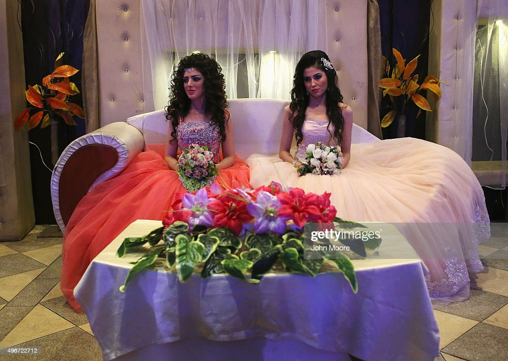 Kurdish brides Halbast Khalili, 21, (L), and Mezgin Murat, 21, (C), sit on the chez lounge of honor during a wedding reception without their grooms on November 11, 2015 in Qamishli, in the autonomous region of Rojava, Syria. They married their husbands in absentia two months after the brothers successfully immigrated to Germany in the arduous journey as refugees. The women plan to join their husbands in Europe once their immigration documents have been processed.
