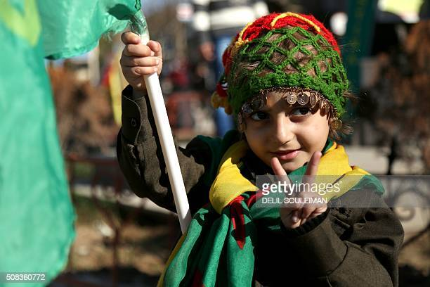 A Kurdish child flashes the sign for victory during a demonstration against the exclusion of SyrianKurds from the Geneva talks in the northeastern...