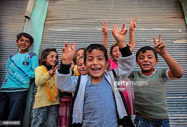 Kurdish children chant slogans and flash V signs in the besieged Kurdish city of Ain al-Arab , September 30, 2014 in Kobane, Syria. Islamic State...