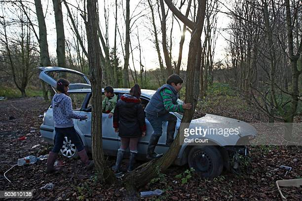 Kurdish children play in an abandoned car in a new migrant camp on January 6 2016 in Dunkirk France Thousands of migrants continue to live in...