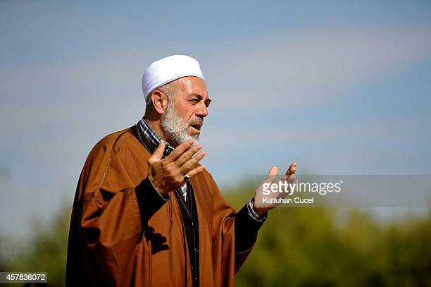 A Kurdish cleric prays for Kobani on October 25 2014 in the southeastern town of Suruc Sanliurfa province The Syrian town of Kobani has yet again...