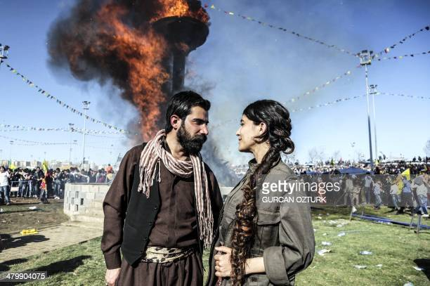 A Kurdish couple looks at each other romantically in front of a Newroz fire as they celebrate the Kurdish New Year on March 21 in the southeastern...