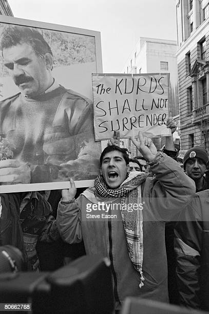 Kurdish demonstrators hold a portrait of Kurdistan Workers Party leader Abdullah Ocalan as well as a placard reading 'The Kurds Shall Not Surrender'...