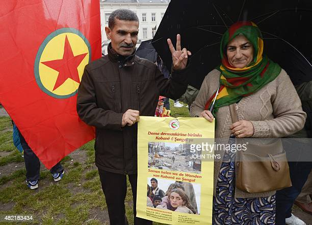 Kurdish demonstrators hold a poster depicting destruction in the Syrian town of Kobane and refugees as they gather for a protest against the Turkish...