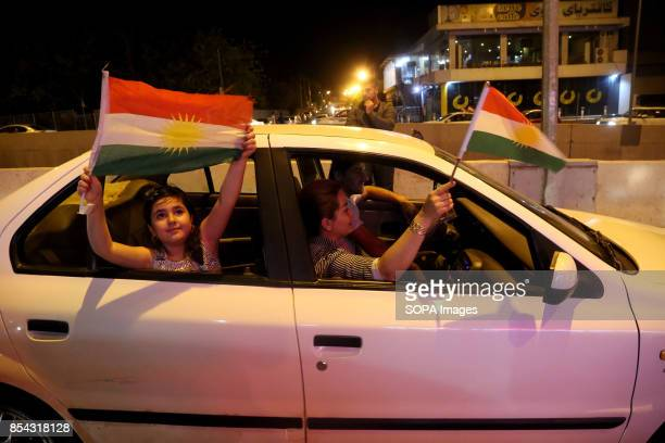Kurdish family is seen inside their car while holding Kurdish flags and celebrating the referendum during the night September 25 2017 is a historic...