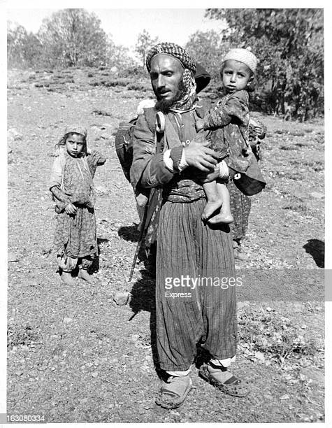 A Kurdish father carrying his child as the other follows behind the Kurdish people are descendants of Medes whose origins are in the Middle East the...