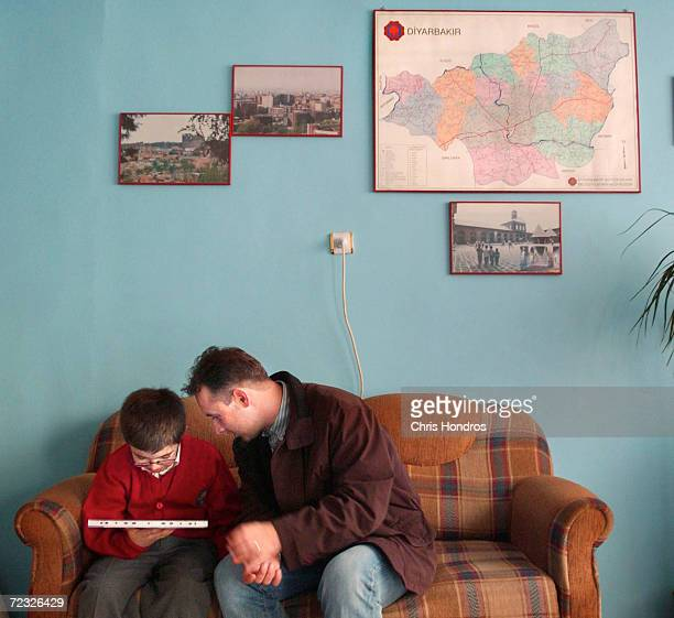 Kurdish father helps his son witha lesson under a map of the Kurdish areas of Turkey January 8 2003 in Diyarbakir the capital of the region...