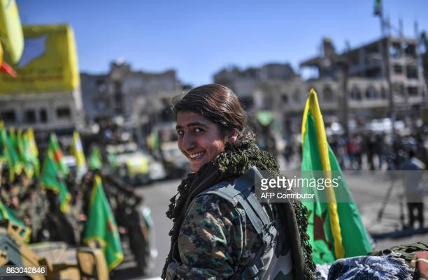 A Kurdish female fighter of the Syrian Democratic Forces takes part in the celebration at the iconic AlNaim square in Raqa on October 19 after...