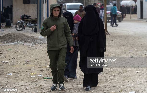 Kurdish female fighter walks next to a woman reportedly the wife of an Islamic State group fighter at the Internally Displaced Persons camp of alHol...