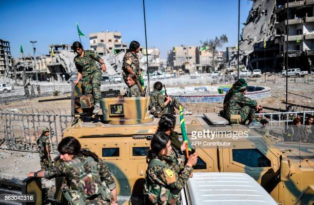 Kurdish female fighters of the Syrian Democratic Forces gather during a celebration at the iconic Al-Naim square in Raqa on October 19 after retaking...