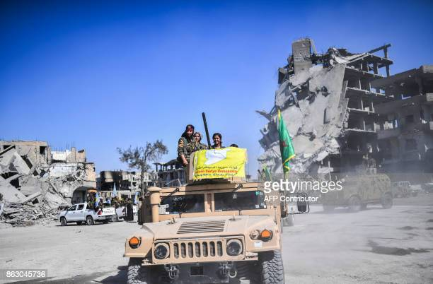 Kurdish female fighters of the Syrian Democratic Forces gather during a celebration at the iconic AlNaim square in Raqa on October 19 after retaking...