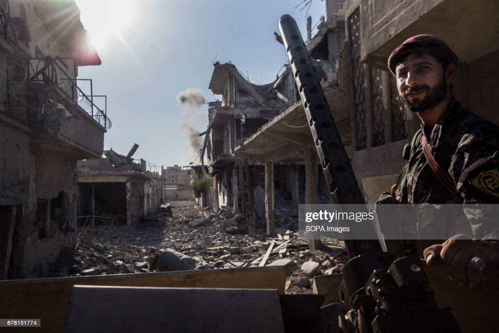 Kurdish fighter from the YPG stands on the humvee as the... : News Photo