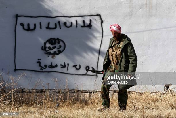Kurdish fighter walks by a wall bearing a drawing of the flag of the Islamic State group in the northern Iraqi town of Sinjar, in the Nineveh...